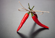 Red hot chili peppers tied twine against dark background Stock Photo