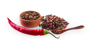 Red hot chili peppers on white backround. With wooden measuring spoon and cup with colore pepper Stock Photo