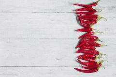 Red hot chili peppers on white wooden background, top view, copy space royalty free stock image