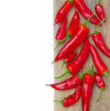 Red hot chili peppers on a wooden board, isolated, close-up Stock Images