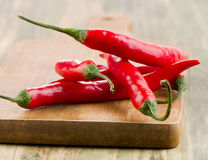Red hot chili peppers on a wooden board Stock Images