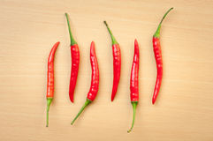 Red hot chili peppers on the wooden desk. Six Red hot chili pepper on cutting board Stock Photography