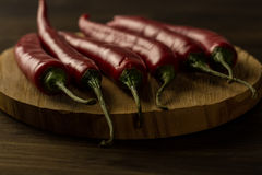 Red hot chili peppers on wooden table Royalty Free Stock Image