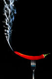 Red hot chilli pepper on fork with smoke Stock Images