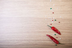 Red hot chilli pepper with sea salt and colored pepper on wooden Royalty Free Stock Photos