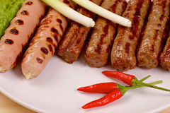 Red hot chilli peppers with grilled sausages and Stock Photos