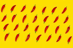 Red hot chilli peppers pattern on yellow background. Flat lay stock photography