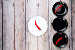Red hot chilli peppers on plate. Red hot chilli pepper on black and white plates Royalty Free Stock Image