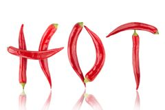 Red hot chilli peppers spelling the word. `hot`. Red and spicy chili pepers creating a word hot on white background royalty free stock image