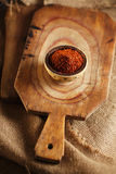 Red hot chillies pepper  flakes in bowl on wooden board Royalty Free Stock Photos