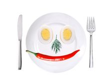 Red hot chilly pepper and two eggs on white plate isolated Royalty Free Stock Image