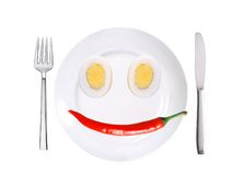 Red hot chilly pepper and two eggs on white plate isolated on wh Stock Image
