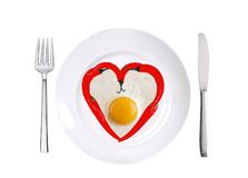 Red hot chilly peppers and fried egg on white plate isolated Stock Photography