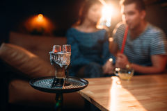 Red-hot coal on hookah in night club. Young couple smokes tobacco, smoking and night relaxation stock photo