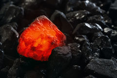 Red hot coal nugget on focus on other cold raw nuggets of coal. Background of raw coals with soft focus exclusion with color and t. Emperature stock photo