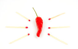 Red Hot Fiery Chili Pepper. A red chili pepper surrounded by multiple match sticks indicating a very hot chili Stock Image