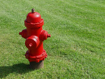 Red Hot Fire Hydrant. A bright red fire hydrant stands on a lush green lawn in Ottawa, Canada stock photography