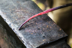 Red hot glowing steel rod on anvil close up Royalty Free Stock Photo