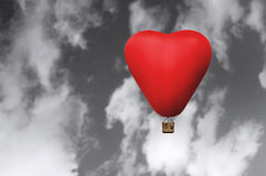 Red hot hair balloon in the shape of a heart. Red hot air balloon in flight against a black and white sky Royalty Free Stock Photos