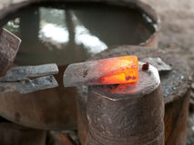 Red hot head of ax at a blacksmith's workshop Stock Photos