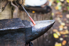 Red hot heated iron rod on anvil Stock Photo