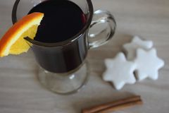 Red hot mulled wine with orange slice and white stars cookies and cinnamon stick unfocused top view. Winter hot drink. Red hot mulled wine with orange slice and Stock Photo