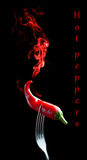 Red hot pepper. On a fork with smoke on black background Stock Photo