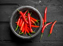 Red hot pepper in bowl. On black rustic background stock image