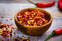 Red hot pepper flakes in a wooden mortar and pepper pods on wooden table royalty free stock photography