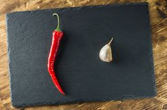 Red hot pepper and garlic diagonally against the background of slate. Top view Stock Images