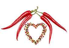 Red hot pepper. Peppers in pods, red hot and colorful mixture of peppercorns, concept of love. Multicolored peppers peas in heart shape, food closeup. Isolated Stock Images
