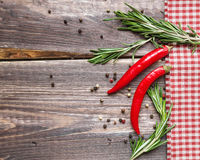 Red hot pepper and rosemary on the rustic wooden background. Red hot pepper and rosemary with checkered napkin on the rustic wooden background Stock Photos