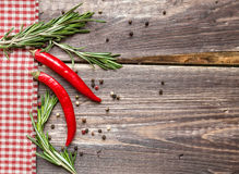 Red hot pepper and rosemary on the rustic wooden background. Red hot pepper and rosemary with checkered napkin on the rustic wooden background Stock Image