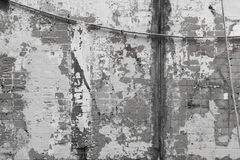 Black and white image of brick wall, background. Texture. Wall fragment with stains of old paint, rope, pipe royalty free stock photo