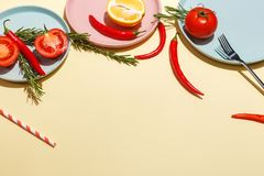 Red hot peppers, tomatoes, rosemary and spices on ligth-yellow background. Table setting. Top view stock image