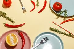 Red hot peppers, tomatoes, rosemary and spices on ligth-yellow background. Table setting. Top view stock photos