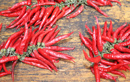 Red hot peppers on wooden table at  market Stock Photo