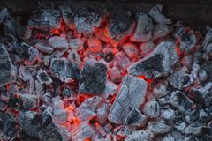 Red-hot pieces of coal and the flames in the brazier for cooking food. Red-hot pieces of coal and a flame in the brazier for cooking. Lovely background royalty free stock image