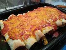 Hot chicken enchiladas in a hot baking tray stock images