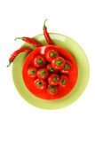 Red hot spicy peppers. On the red and green plates Stock Photography