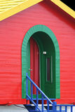 Red House. A colorful house. It's red, with a green door, a yellow roof and blue stairs. This is a holiday home by the sea. It's very cheerful stock photo