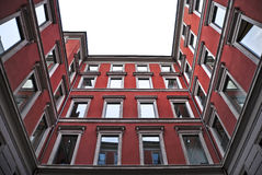 Red house apartment. Wide angle shot of a red classic building palace courtyard Stock Photos