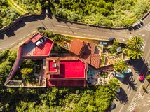Red house and big garden shoot by drone. Road on the side and palms in Tenerife royalty free stock images