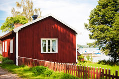 Red house and boats. Front view of a red swedish house near a lake with boats Royalty Free Stock Photo