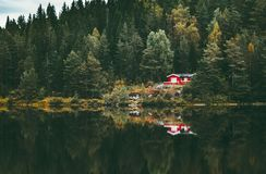 Red house in coniferous Forest with lake water reflection Landscape. In Norway Travel serene scenic view scandinavian wild nature Stock Image