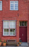 Red house and door with a bench in front of it Royalty Free Stock Image