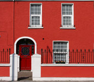 Red house facade. Facade of a red house with white windows Royalty Free Stock Images