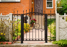 Red house facade with iron fence, green trees and flowers.  Stock Image