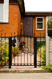 Red house facade with iron fence, green trees and flowers.  Stock Images
