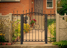 Red house facade with iron fence, green trees and flowers.  Royalty Free Stock Images